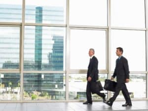 Two Businessman Workers Comp Mentor Walking By Office Window