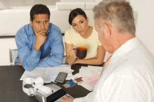 Businessman Assisting Couple Work Comp Tax Question At Home