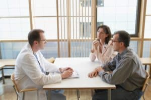 Couple Talking To Physician Dispensed Meds On Table