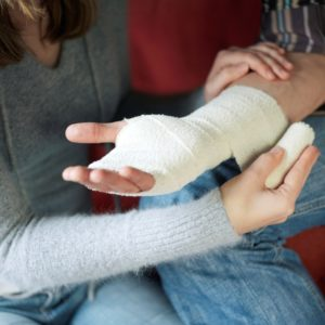 Woman Wrapping Man Hand Progressive Insurance Workers Comp Injured
