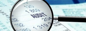 Magnifying glass work comp claims department on audit paper