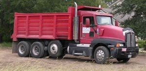 Picture of red triaxle dump truck outside