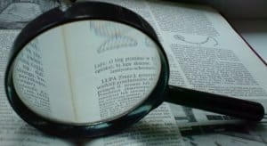 Open Book of workers comp policy questions with magnifying glass above