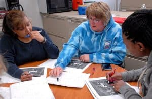 Picture of three women workers comp policy questions reviewing papers