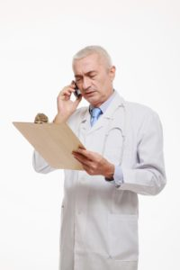 Doctor talking on Phoned In FROI while looking at clipboard