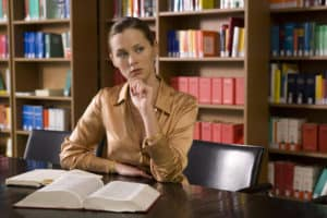 Woman with book Workers Comp Medical Network studying at desk in library