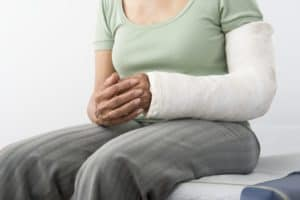 Senior woman Workers Comp Claim Denial sits with plaster cast on broken arm