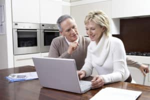 Middle-aged couple working Account for Coronavirus Furloughed on laptop in kitchen