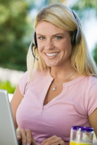 Woman using laptop Telecommuting Class Code 8871 wearing headset