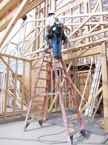 Construction man insurance blogging on the ladder