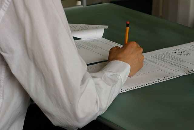 Student hand writing workers comp benefits info exam at classroom